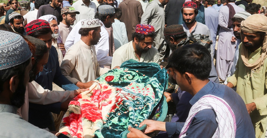 Men carry a body, who was killed following an earthquake, during a funeral in Harnai, Balochistan, Pakistan, October 7, 2021.