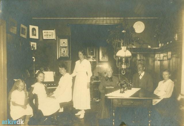 Fotografi i brune nuancer af familien Nielsen i deres stue på adressen Svinget 3