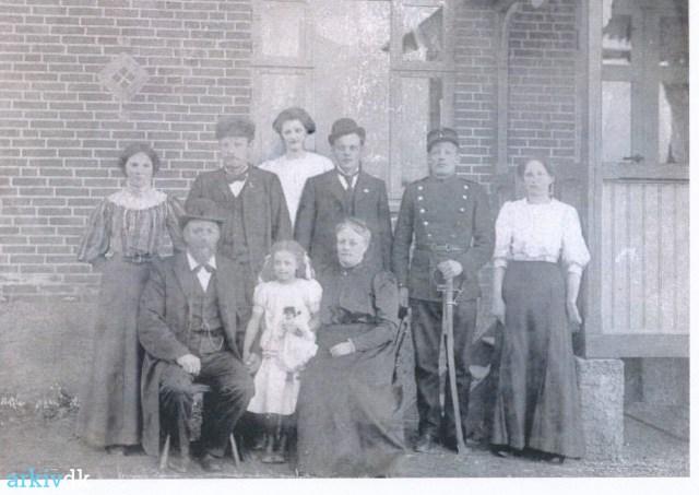 Fotografi i gråtoner, familiefoto foran hus, de seks i bagerste række står op, de tre i forreste rækker sidder ned.