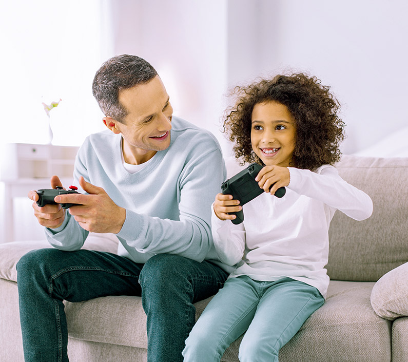 cheerful little girl playing console with dad
