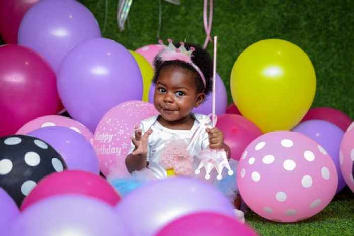 A little girl wearing a tiara celebrates her birthday among colorful balloons
