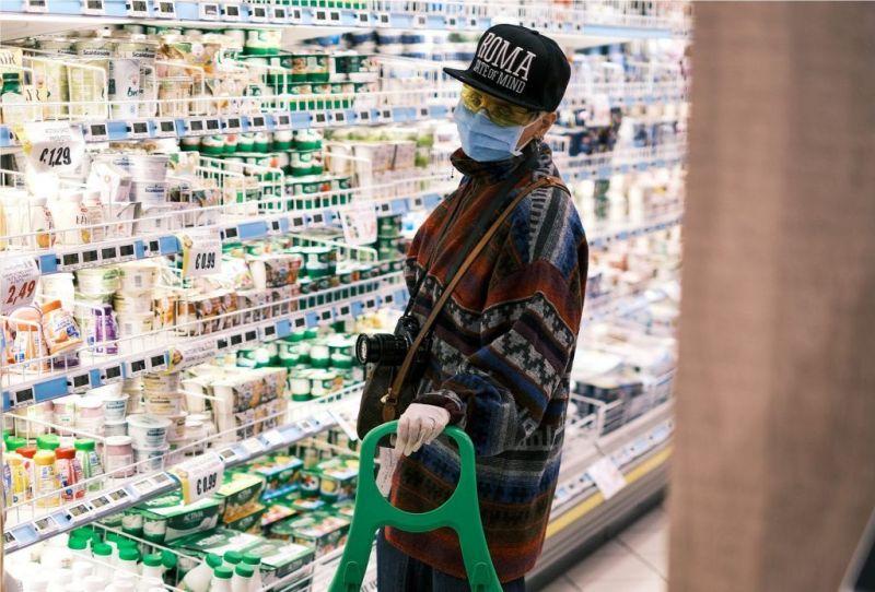 mujer haciendo la compra estos días en un supermercado en Italia, protegida con guantes y mascarilla, en plena crisis del coronavirus