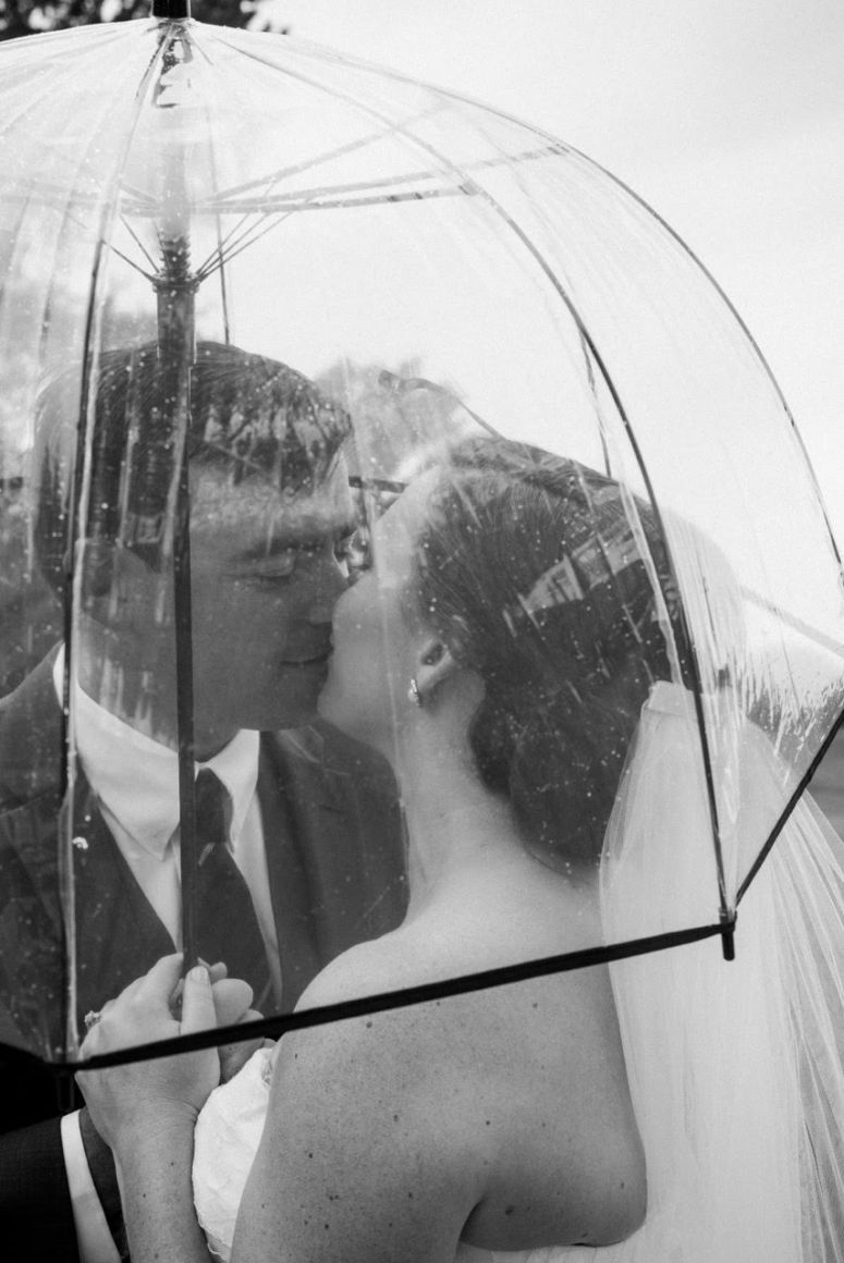 Bride and Groom Under Umbrella on Wedding Day