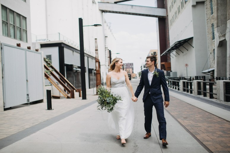 bride and groom walking down city street