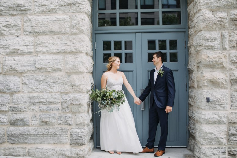 bride and groom in front of blue door