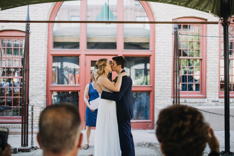 bride and groom first kiss at intimate wedding