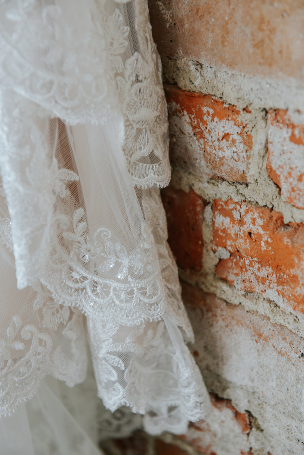 Bridal Gown hanging on exposed brick wall