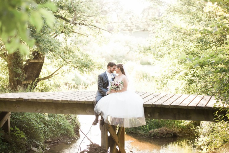 bride and groom on bridge over lake