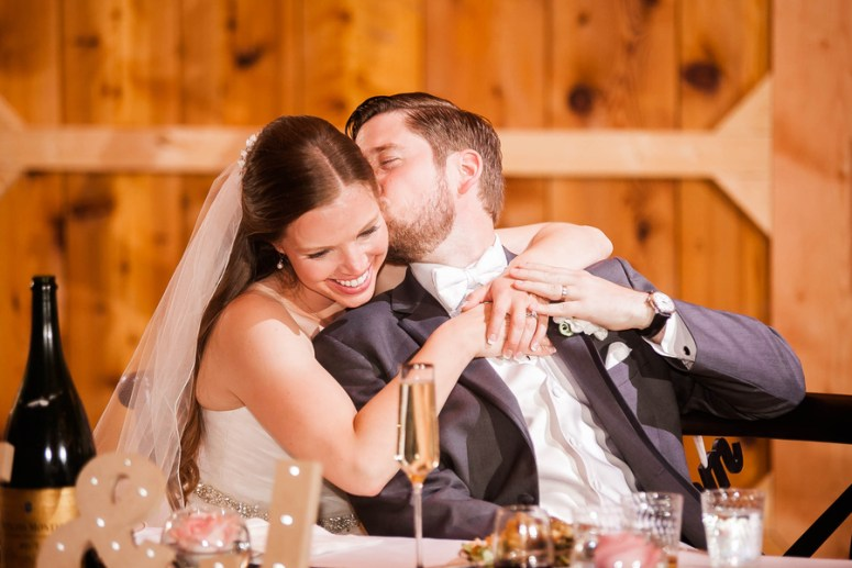 bride and groom sitting at sweetheart table