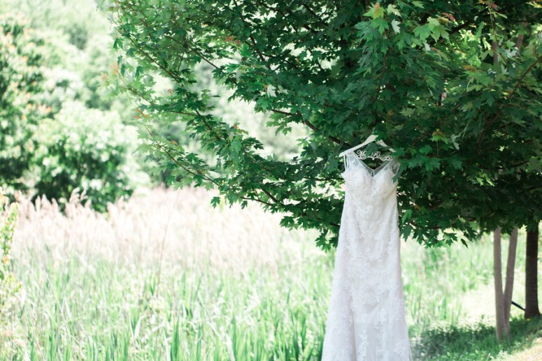bridal gown hangning in field
