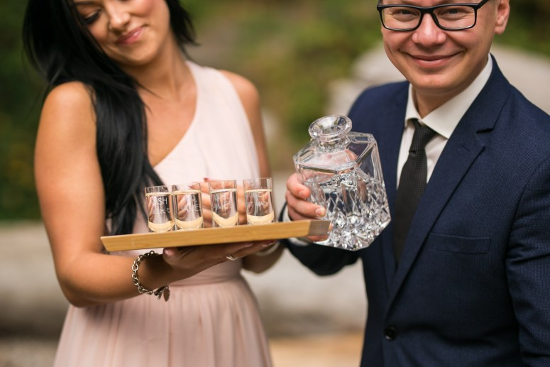maid of honor and best man pouring shots at wedding