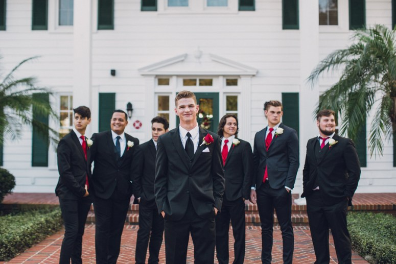 groomsmen with three piece suit and red ties
