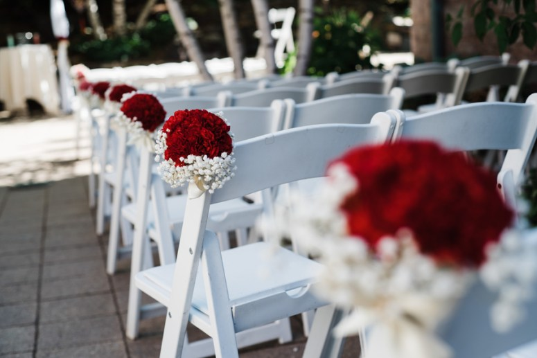 Outdoor wedding ceremony with white folding chairs