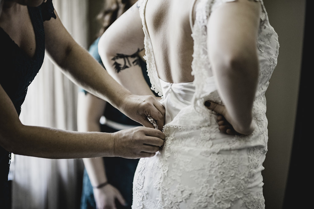 bride getting dressed buttoned up photo
