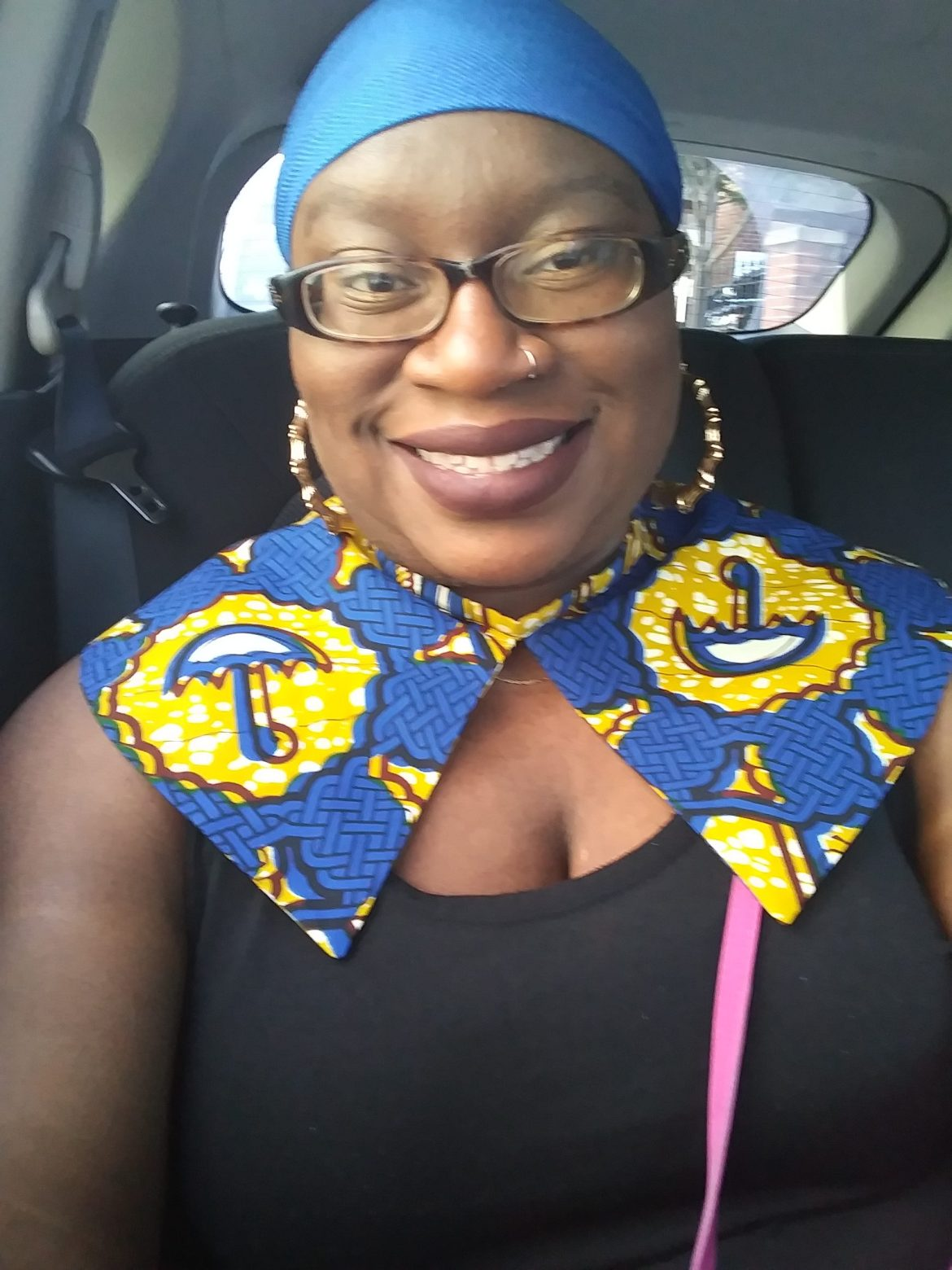 Ann Marie in a car wearing an african collar and headwrap
