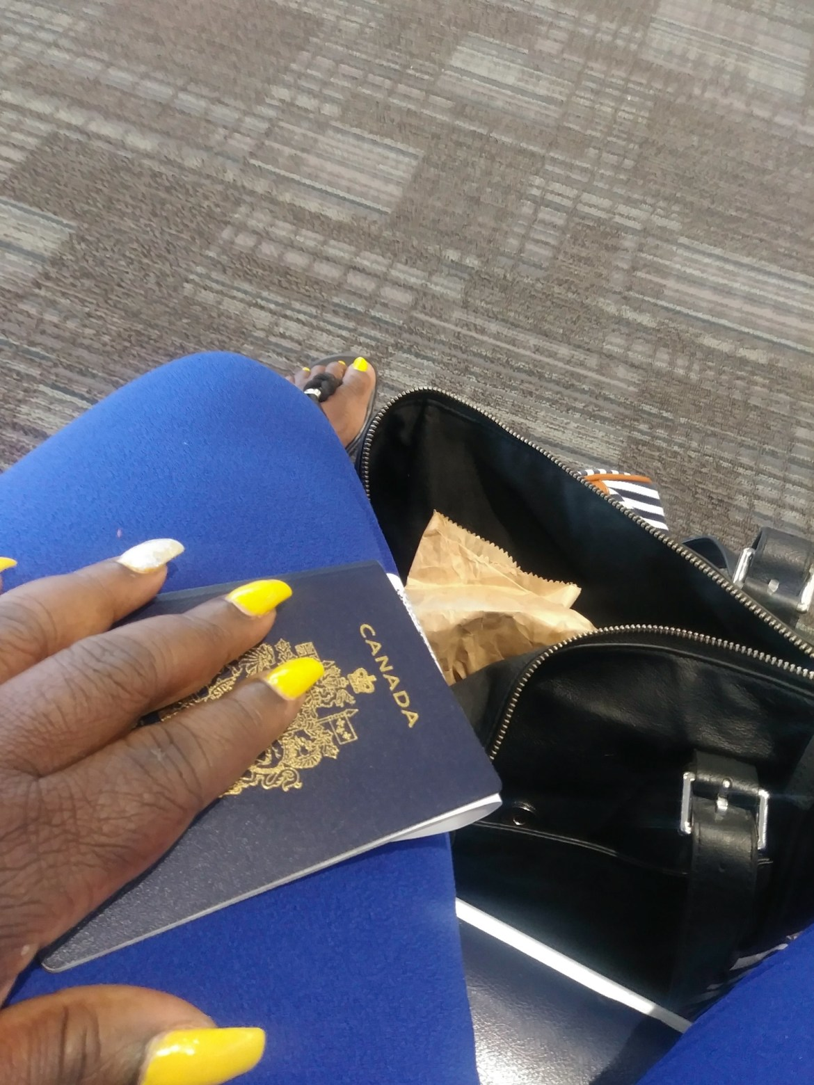 Holding a passport with yellow nails on a blue backround