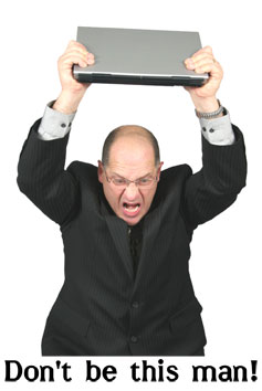 An apparently Angry Man about to throw a laptop into the floor