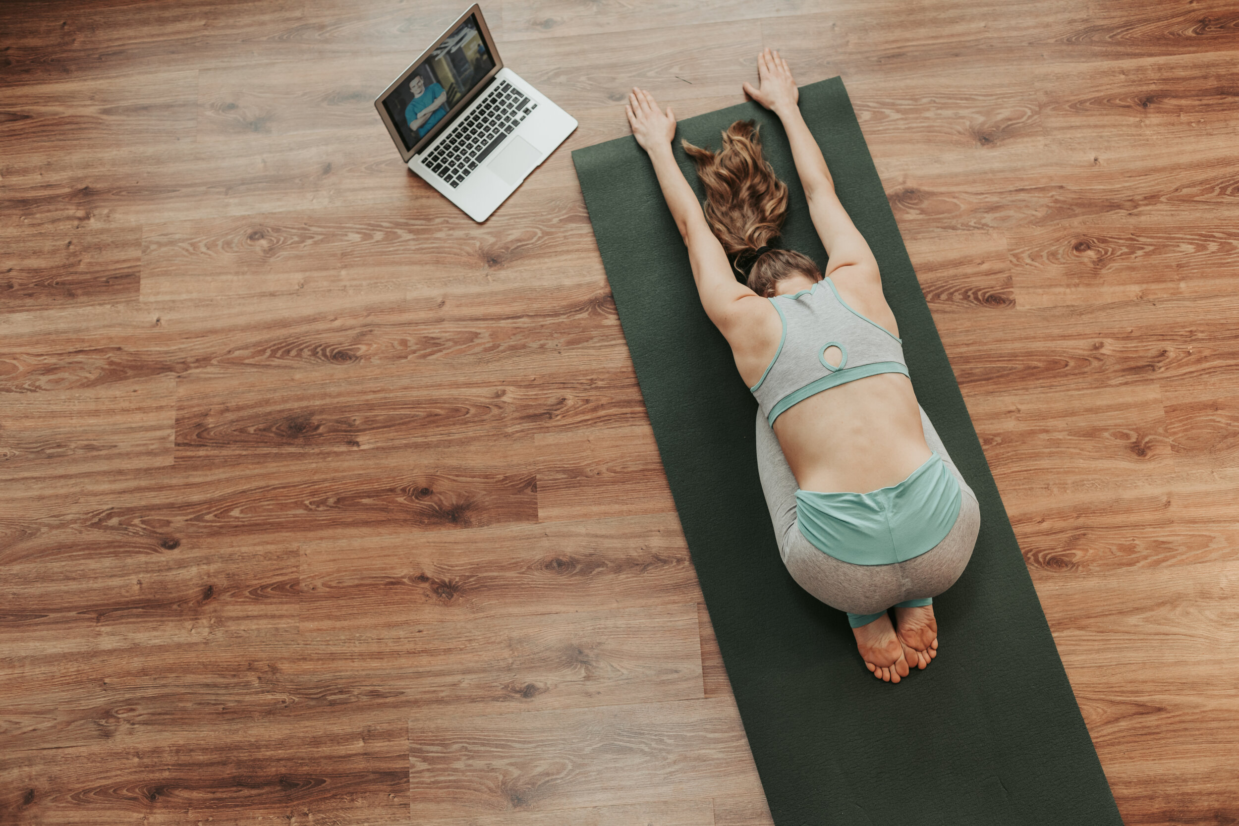 Health practice concept. Top view portrait of young balanced woman in sportswear doing child's yoga pose on mat at home with notebook beside