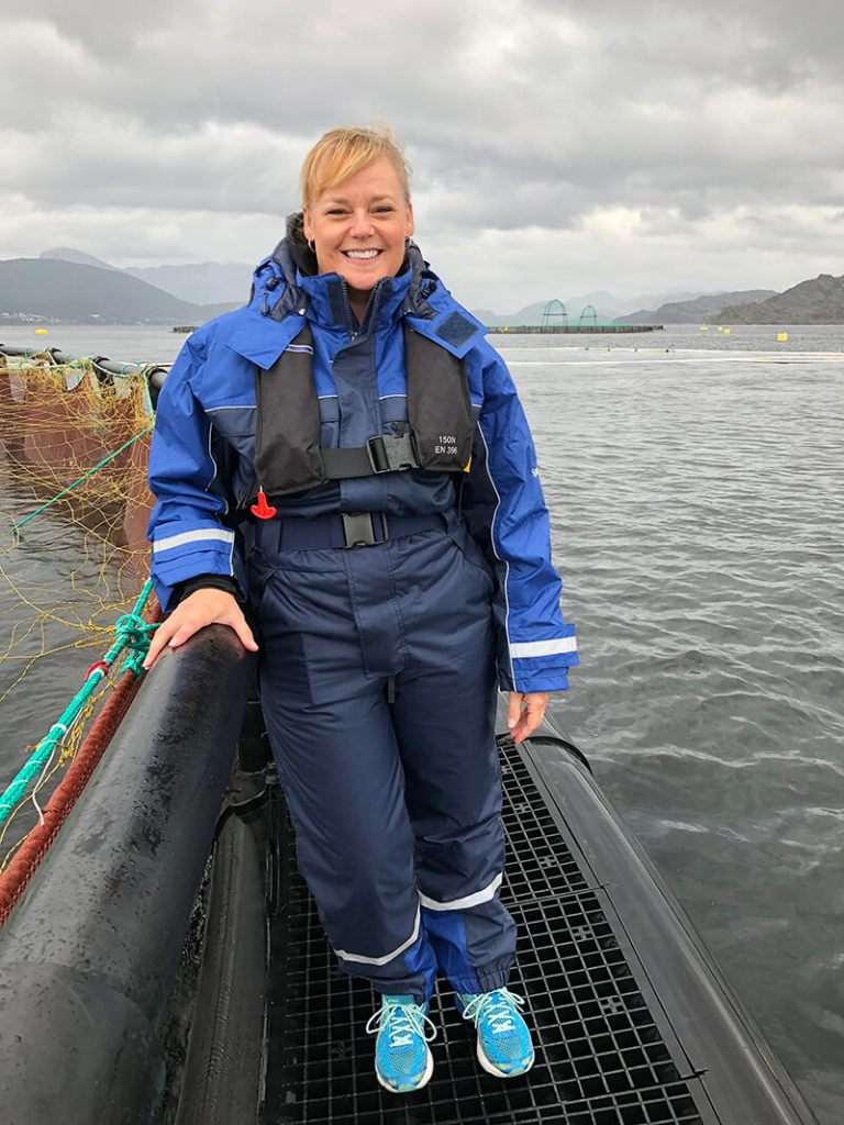 Standing on the edge of the salmon pen in the fjord at Steinvik Fiskefarm, Eikefjord