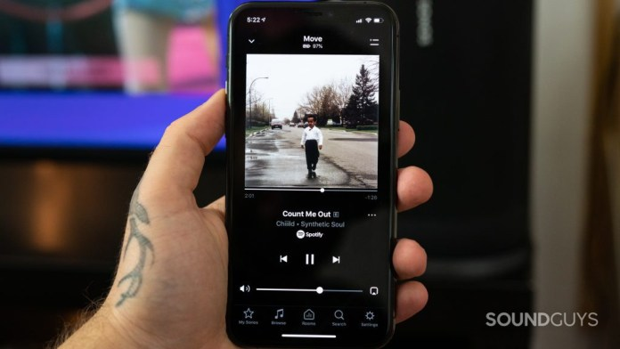 Man holding iPhone 11 Pro with music playing in Sonos app