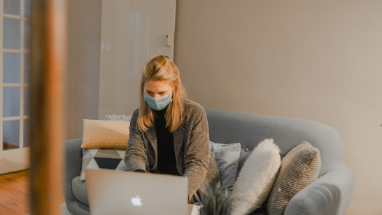 woman on couch wearing a mask in front of a computer looking for a new job
