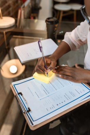 woman at a table with a resume on a clipboard writing on a post it note.