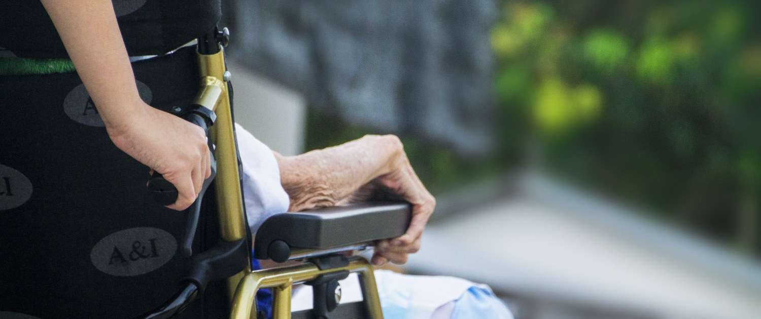 A caregiver pushes a wheelchair with an elderly person in it.