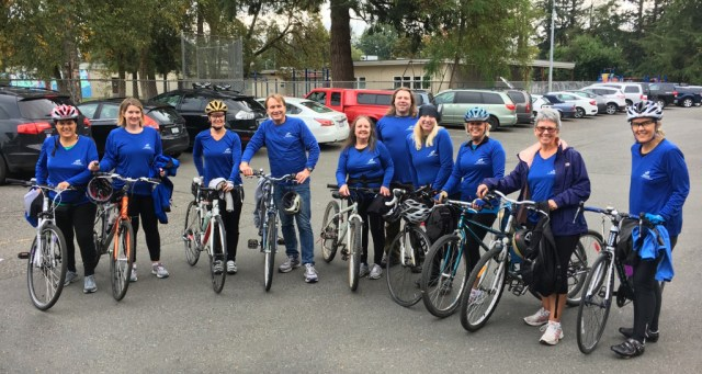 A dozen cyclists donning blue shirts with the Sources logo