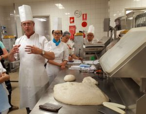 Boris and Laurie showing students how to mold the dough.