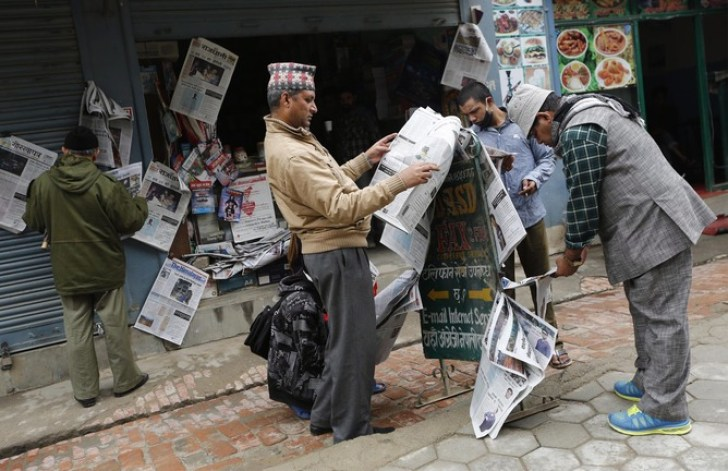 epa04727068 People catch up with the news at a kiosk in the street in the aftermath of the earthquake that struck 25 April, Kathmandu, Nepal, 30 April 2015. The number of people killed in the 7.8-magnitude earthquake and the subsequent aftershocks has reached 5,489, said Govardan Karki, an official at the National Emergency Operation Center.  EPA/ABIR ABDULLAH