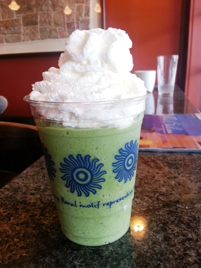 Trying a Matcha Green Tea Latte, blended with ice and topped with whipped cream.