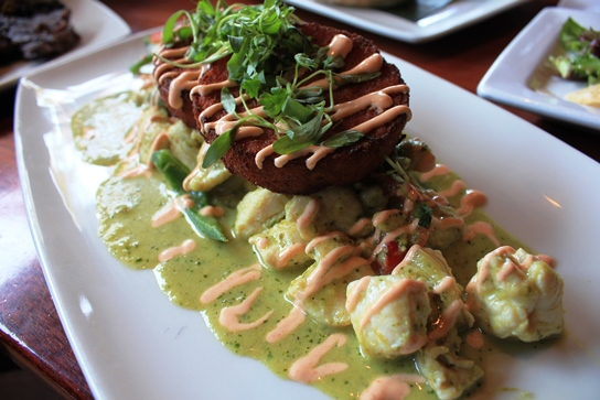 Lazy Dog Chicken Poblano with tamle cakes, a fusion of mexican tamales and polenta cakes.  The impossibly tender chicken and creamy pablano sauce elevate this dish above all others.