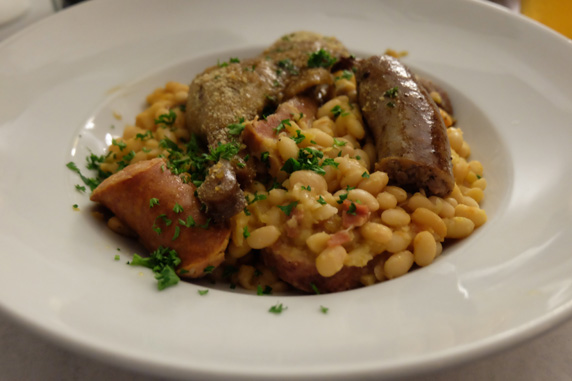 The plated cassoulet with white beans, Toulouse, Monbeliar and French garlic sausage, pork belly and duck confit.