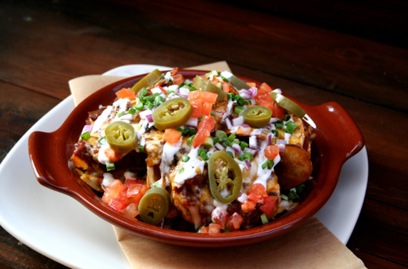Irish Nachos: fried potatoes covered in Lazy Dog Chili topped with Jack and Cheddar cheeses, sour cream, onions, tomatoes, and house-made pickled jalapenos.