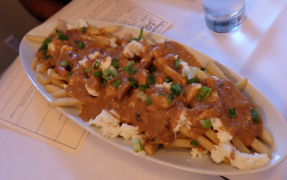 Hearty poutine with cheese curds topped with green onions