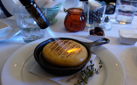 A torch is applied to a wheel of camembert cheese