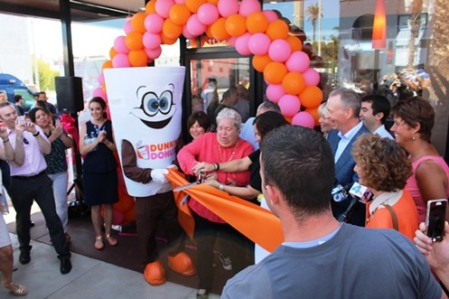 Santa Monica mayor Pam O'connor and the Dunkin' Donuts mascot do the official ribbon cutting.