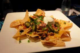 Tortilla chips piled high, layered with a three bean mix, Monterey Jack, cheddar cheeses, freshly made pico de gallo, jalapenos, green onions and sour cream is named the 'Nachopalooza'