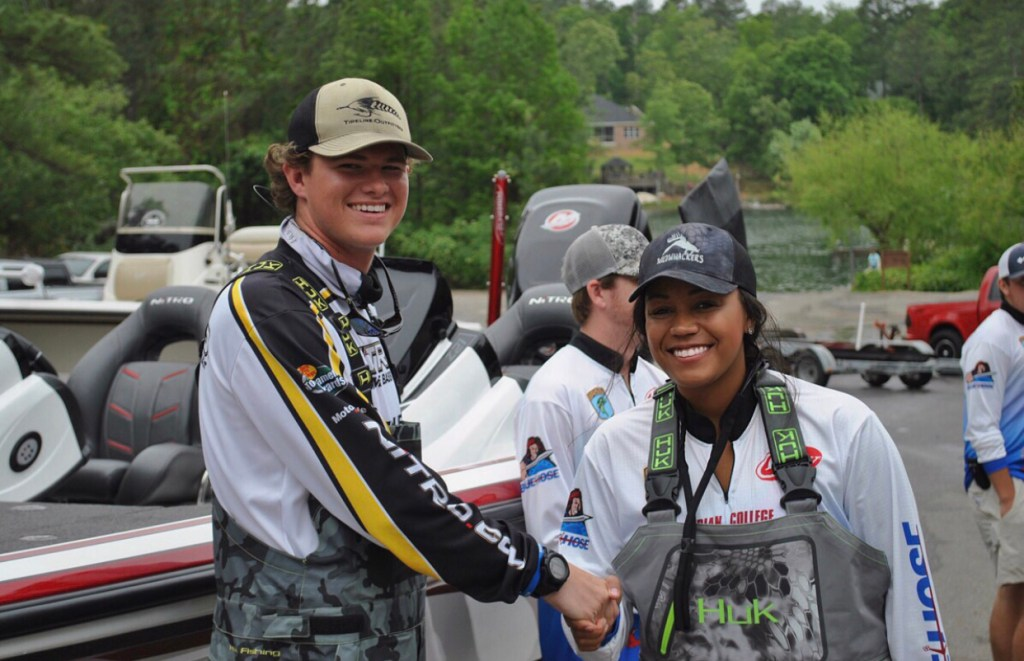 A young man (Andrew Snelgrove) and young woman (Anastasia Patterson) shaking hands at a fishing tournament.