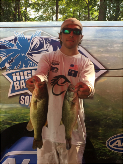 A young man in sunglasses holding two Bass.