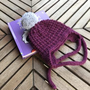 Damson earflap hat with grey pom pom