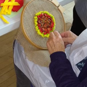 hands holding a embroidery ring with hessian on and using yellow and orange material to make rag rug