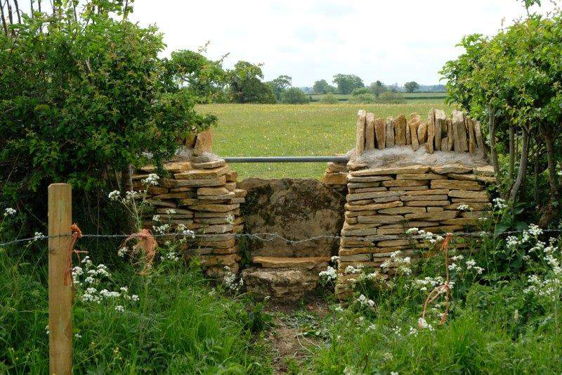 Stile recently refurbished by the Wardens - farmer still prefers a  strand of barbed wire