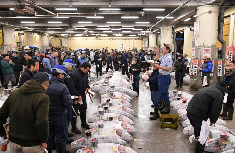 An auctioneer starts its new year auction of the frozen tuna at the Tsukiji fish market in Tokyo on January 5, 2018. The famous market opened its doors for public viewing of their tuna auction one last time on Friday before moving to the new location in Toyosu. (AFP/Kazuhiro Nogi)