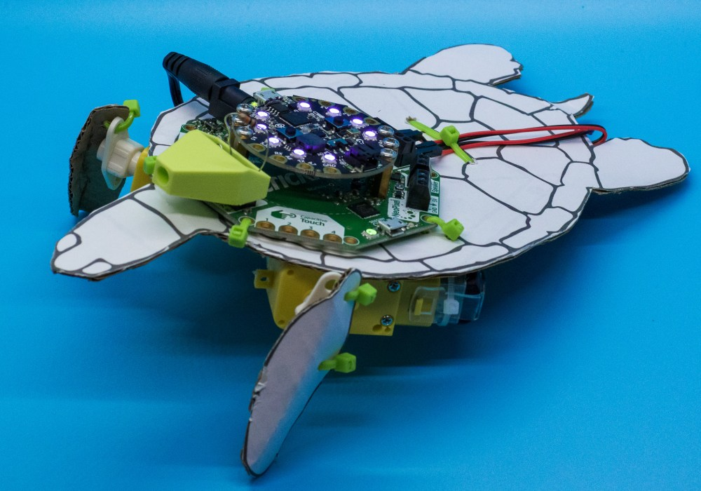 A sea turtle robot looking fearsome on a blue background.