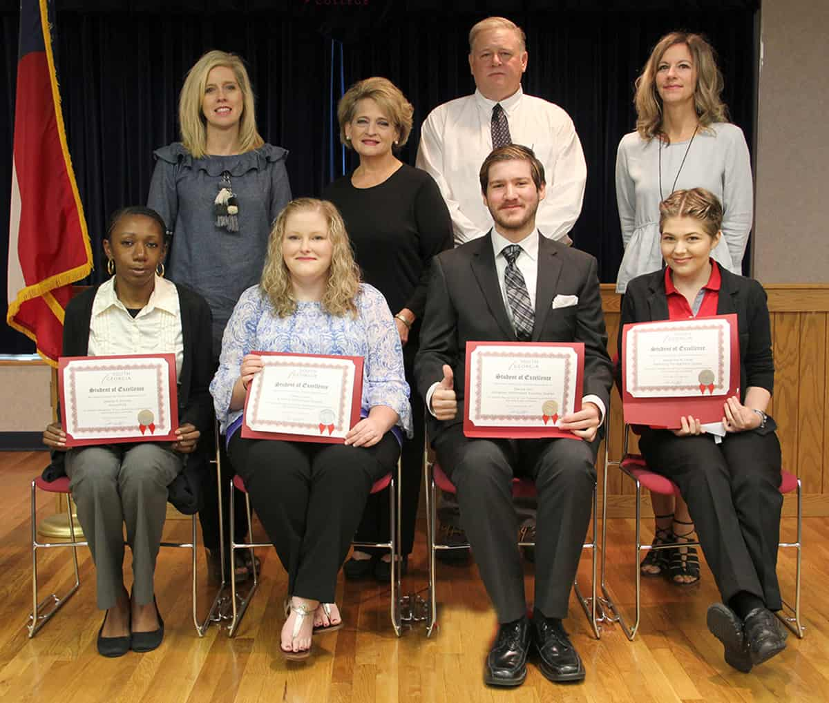 Student of Excellence nominees sit in chairs in front of their nominating instructors. Seated from left to right are: Desiray Kenney, Callie Collier, Dakota Hall, and Alexandra Joiner. Standing left to right: Teresa Jolly, Karen Bloodworth, Randy Greene and Lisa Penton.