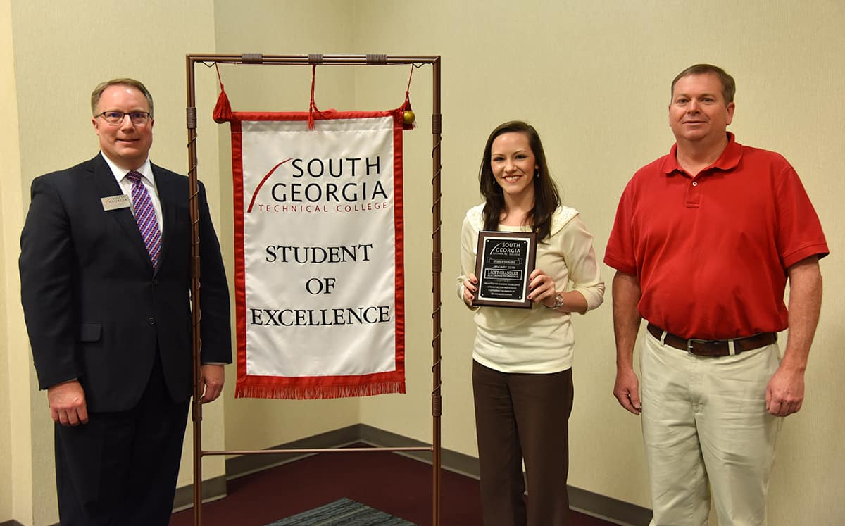 Student of Excellence winner Lacey Chandler (center) stands with nominating instructor Mike Collins (right) and SGTC Vice President of Academic Affairs David Kuipers (left) beside the Student of Excellence banner.