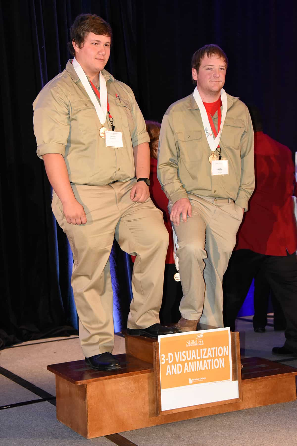 Two males stand on a three tiered podium.