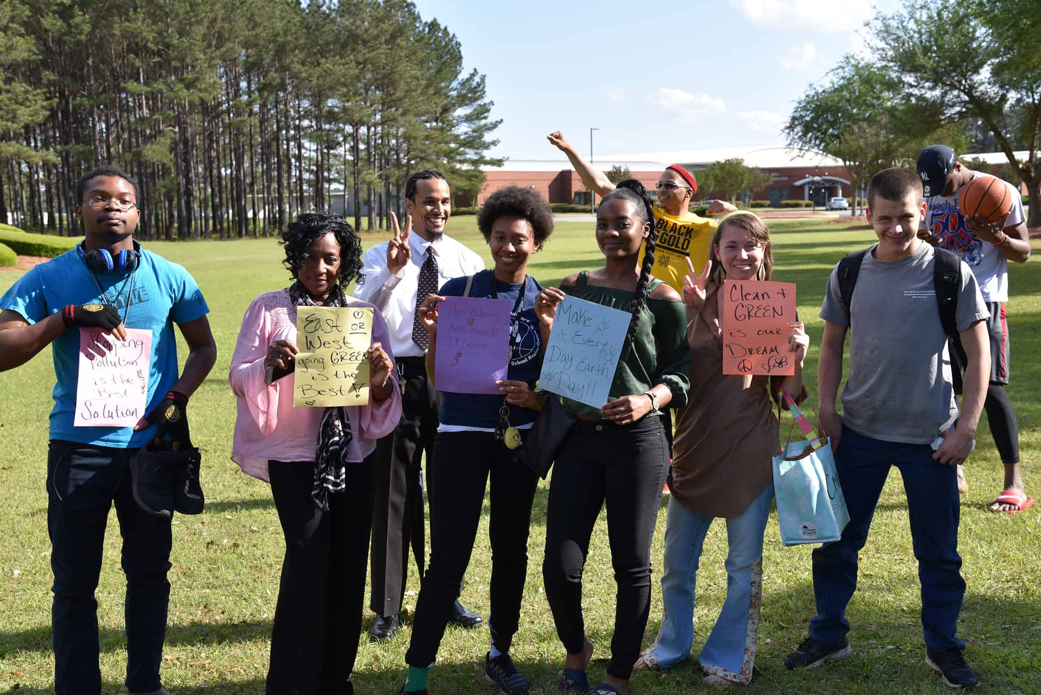 A group of people stand together, holding up signs made of construction paper.