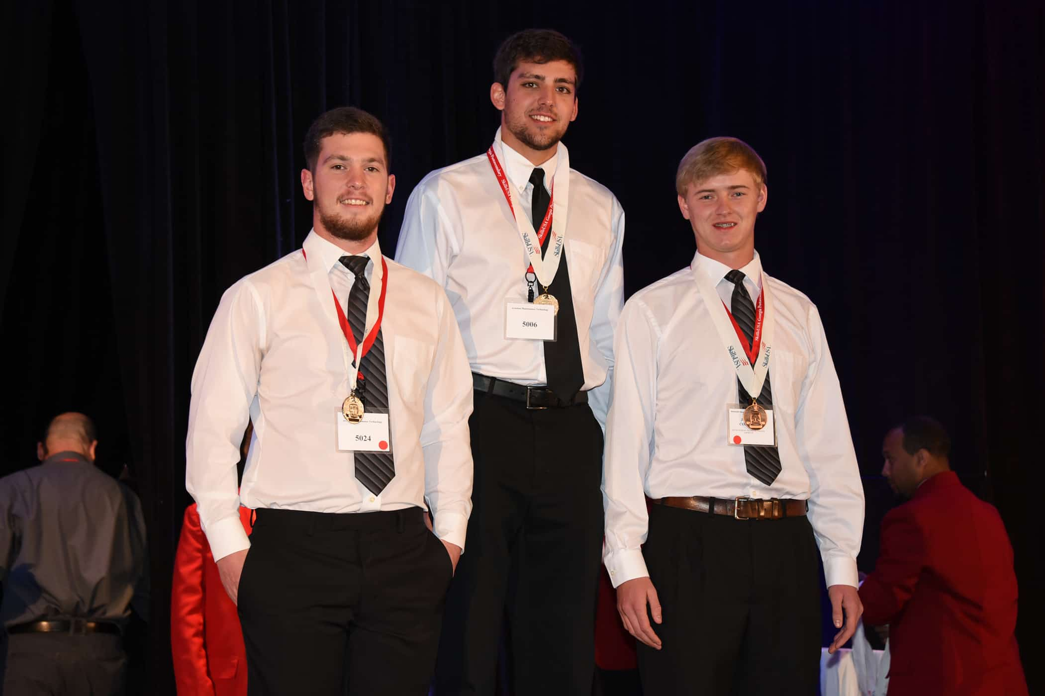 Three white males stand on top of a podium. The center male stands taller.